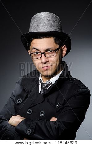 Young man in black coat and hat against gray