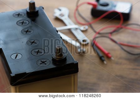 Changing a car battery. Automotive battery on a work desk with testing probe and wrenches in background. Focus on foreground.