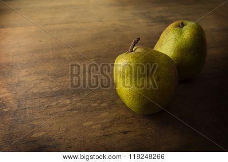 Two pears on rustic wooden table. low key.