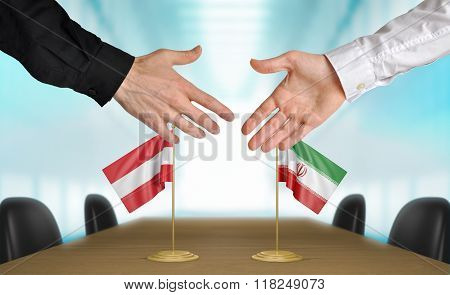 Austria and Iran diplomats shaking hands to agree deal