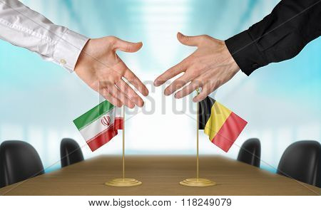 Iran and Belgium diplomats shaking hands to agree deal