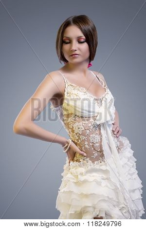 Wedding Dress Concept. Sexy Looking Caucasian Brunette Female Posing In White Tailored Wedding Dress