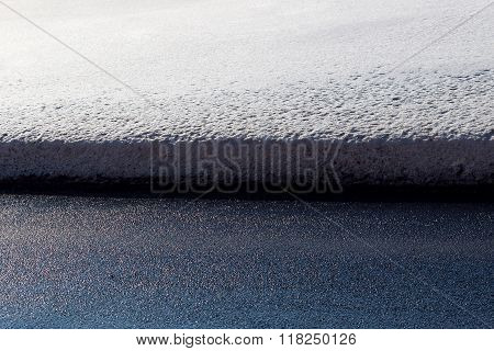 closeup roadside is covered with dirty snow in a winter season