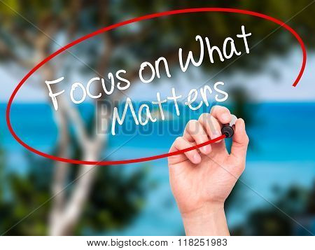 Man Hand Writing Focus On What Matters With Black Marker On Visual Screen