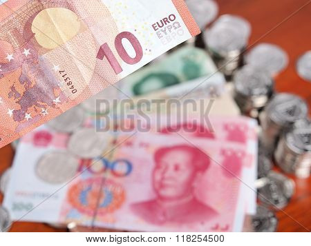 Ten Euro Note In Front Of A Pile Of Coins And Chinese Yuan Notes