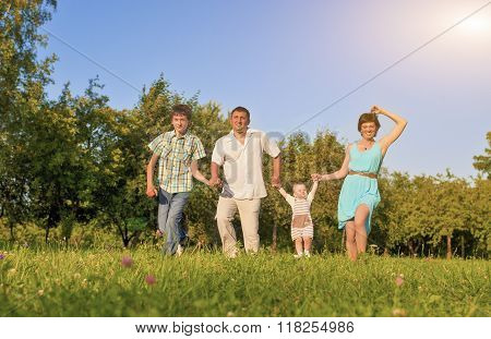 Family Concept And Ideas. Happy Family Of Four Running Together Outside In Green Summer Forest.