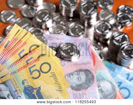 Multiple Fifty Australian Dollar Notes On Front Of A Pile Of Glittering Coins