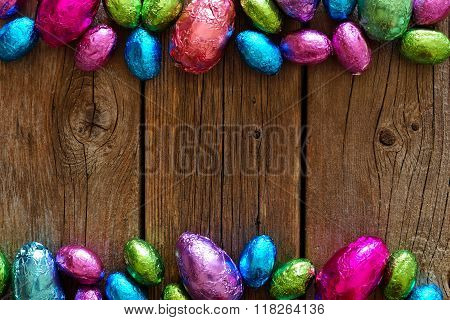 Chocolate Easter Eggs double border against rustic wood