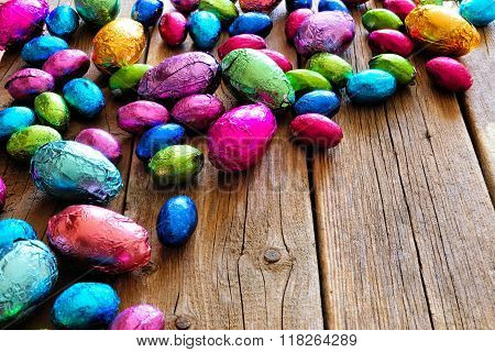 Chocolate Easter Eggs corner border against rustic wood