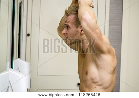 Shirtless, muscular young man looking at his hair in bathroom mi