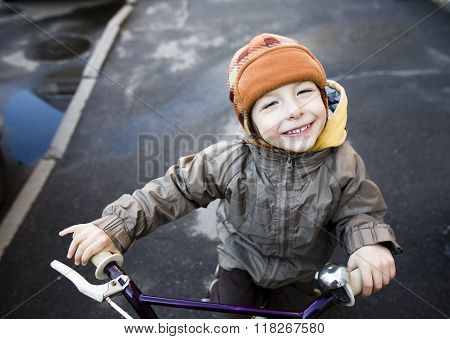 little cute boy on bicycle smiling close up outside