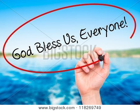 Man Hand Writing God Bless Us, Everyone! With Black Marker On Visual Screen