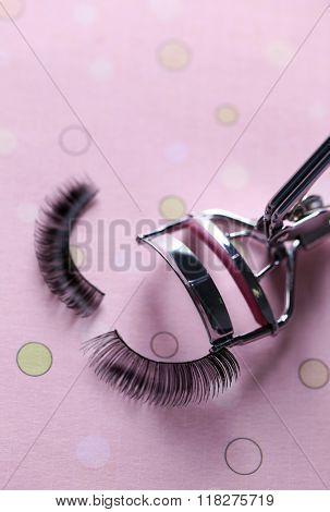 Curler and false eyelashes on a pink background, close up