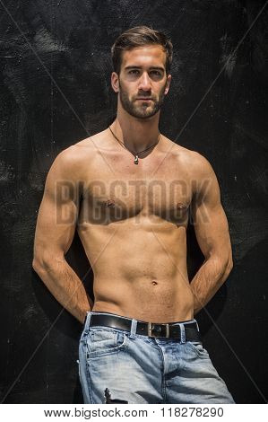 Handsome bearded shirtless young man standing against black wall