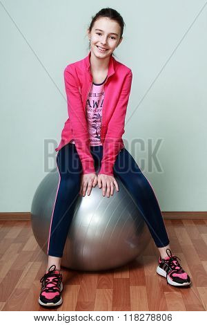 Young Girl In A Pink Blouse Is Sitting On A Fit Ball And Smiling