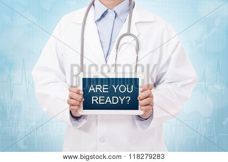 Doctor holding a tablet pc with Are you ready sign on the display