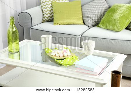 Low table with green bottle, marshmallows and two cups in living room