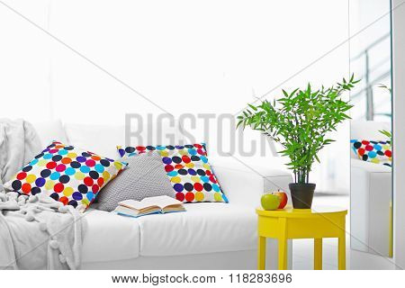 Living room interior with sofa, pillows, yellow chair and green plant