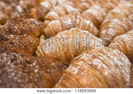 Freshly baked italian croissants (cornetti) background. Low depth of field