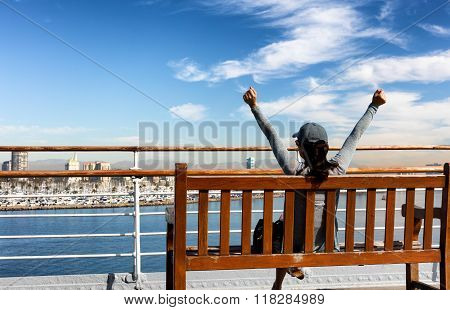 Woman Enjoying The View Of Bay While Stretching Out On Bench