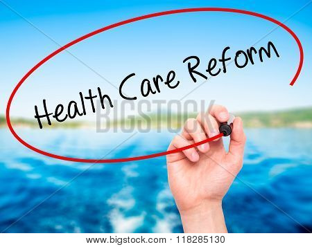 Man Hand Writing Health Care Reform With Black Marker On Visual Screen