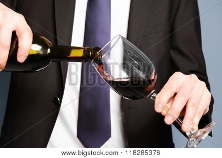 Man in suit pouring red wine into a glass on blue background