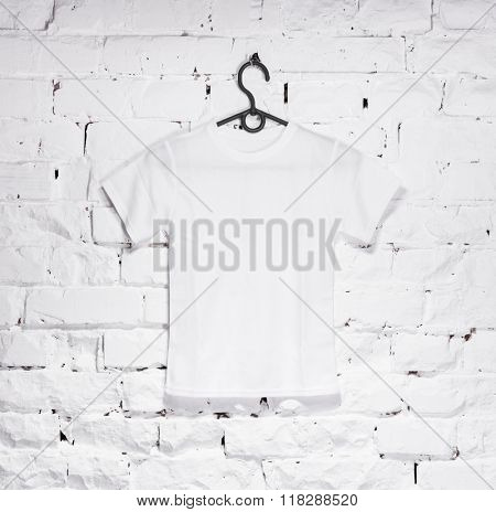 brick whitewashed wall with white t-shirt on hanger