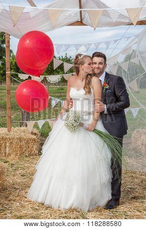 bridal couple newly weds at wedding kissing