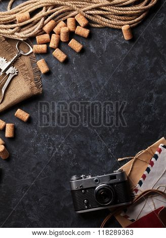 Wine corks, corkscrew, vintage camera and envelopes over dark stone background. Top view with copy space