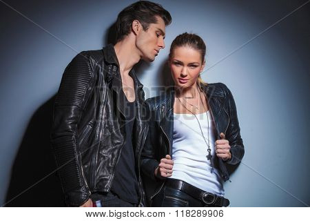 woman in leather jacket takes it off while posing for the camera in studio, boyfriend looks down on her.