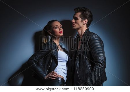 hot couple posing in dark studio background, man looking down on sexy woman in leather jacket