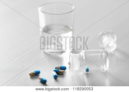 Painkiller capsules spilled from pill bottle and glass of water on the table, close up