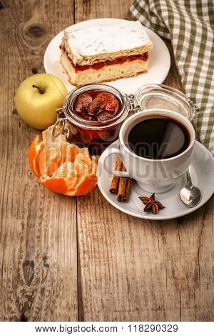 Black coffee in cup with fruits apple tangerine and sweet cake for breakfast