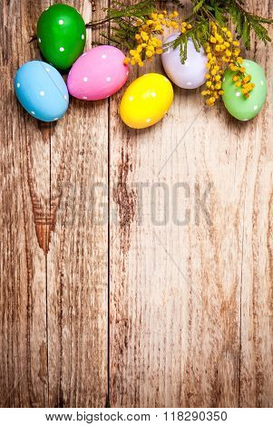 Easter eggs with bunch mimosa copyspace on wooden board