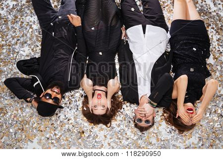 Top view of multiethnic group of funny young friends grimacing and lying on sparkling confetti background