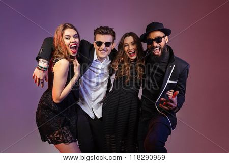 Multiethnic group of cheerful attractive young friends standing and hugging over purple background