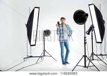 Full length portrait of a young photographer standing with photo camera in studio