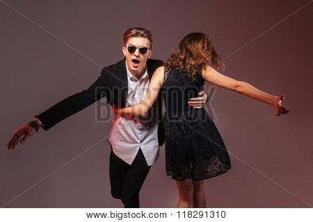 Happy young man and woman dancing and whirling isolated over purple background