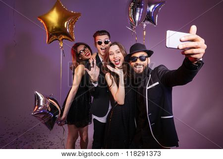Multiethnic group of cheerful friends smiling and making selfie together over purple background