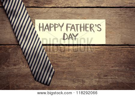 Happy Father's Day inscription with striped tie on wooden background. Greetings and presents