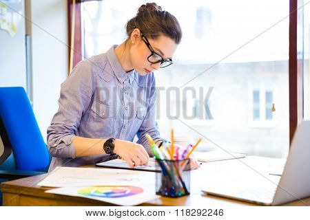 Concentrated pretty young woman fashion designer sitting and drawing sketches in office
