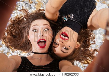Two excited pretty young women with red lips taking selfie and lying on background of shining confetti
