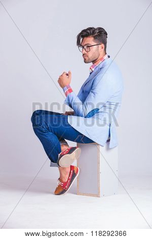 fashionable casual man posing from one side seated on box, with legs crossed while wearing glasses and looking away in studio background