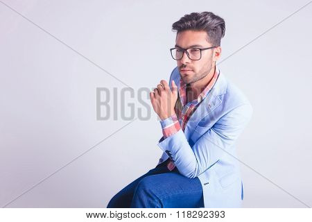 portrait of fashionable man, seated, wearing glasses while thinking and looking away in studio background