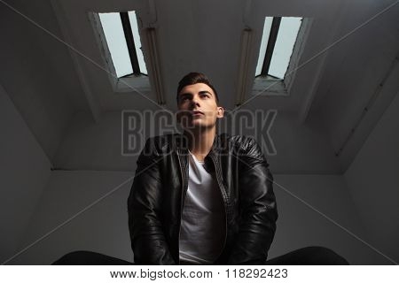 below view of young man in leather jacket posing seated while looking away in gray room