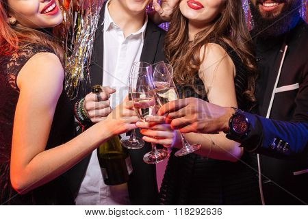 Closeup of bottle and glasses of champagne held by group of happy young friends