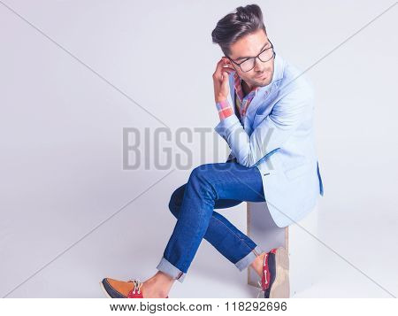 casual young man wearing glasses posing seated with legs crossed, touching his back of the head while looking away in studio background