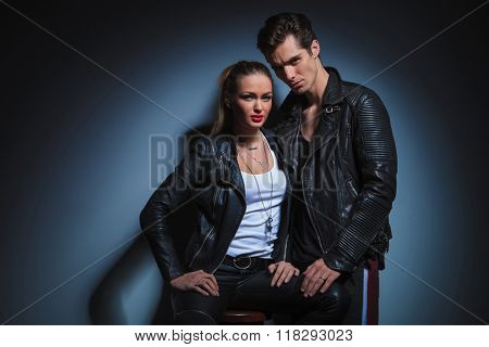 couple in dark leather posing in studio background. the man is posing looking at the camera and touching her leg while the woman sits on a chair looking at the camera.