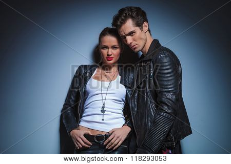portrait of hot couple in leather clothes posing in studio background looking at the camera