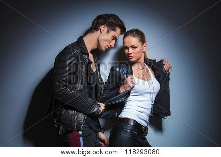 sexy punk woman in leather pose in studio background while boyfriend takes off her jacket